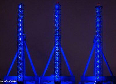 Drei blau angestrahlte Kräne im Hamburger Hafen