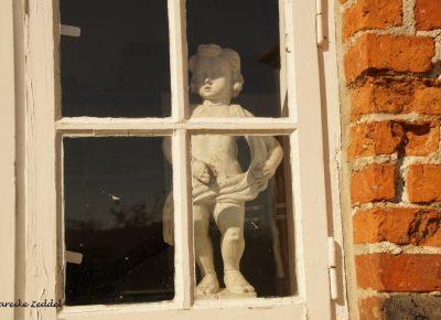 Skulptur schaut aus dem Fenster Kreismuseum Ratzeburg